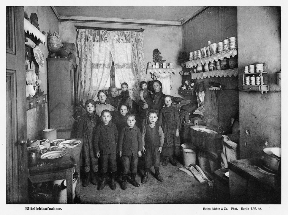 Kitchen. A wretched dwelling comprising a bedroom-cum-kitchen for a family composed of the husband, his wife, and their 10 children ranging in age from 14 to 1½. The oldest of the daughters is absent from this photograph, which does, however, include her grandmother.