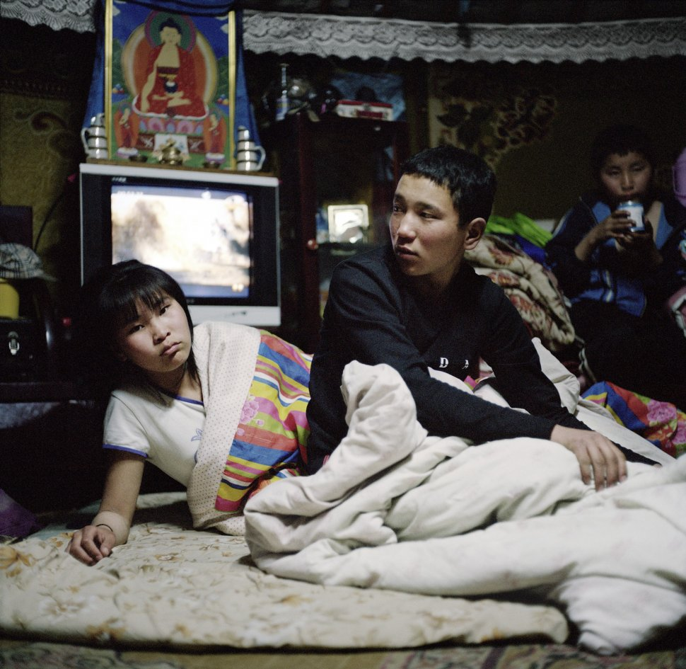 <p>Narantyua and Byambadorj get ready for bed. Some family members sleep in beds located close to the walls; the rest of the family sleep on the floor with blankets. Sleeping arrangements such as these sometimes persist even among families who live in houses or apartments in the city.</p> <p>Bayankhongor, April 2011.</p>